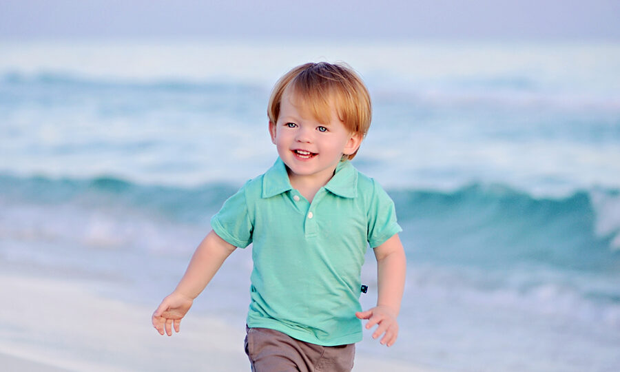Young Boy on the beach in Seaside for a beach photography session